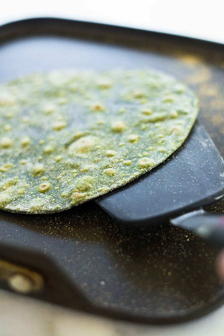 Spatula flipping a cooked spinach tortilla on a griddle. Can see the dark green of the tortilla and golden-brown spots to indicate it's ready.