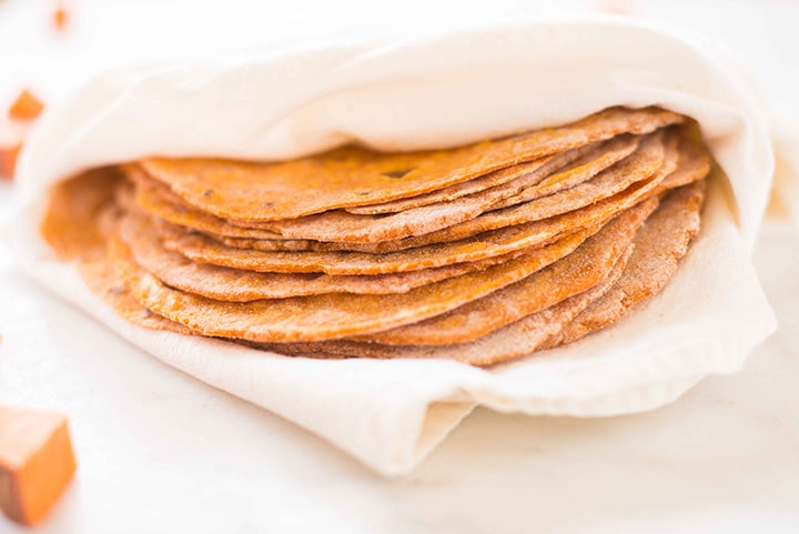 Close up of the cooked sweet potato tortillas which have been piled together and wrapped in a large kitchen towel to stay warm.