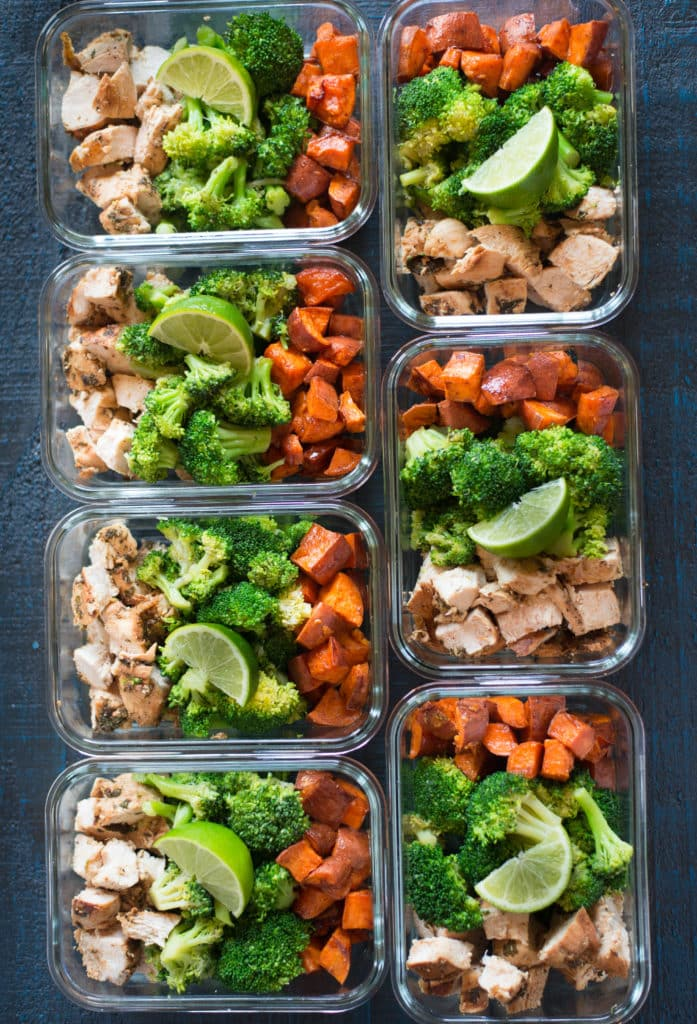 Overhead view of seven meal prep containers containing meal prepped chicken, broccoli, and sweet potatoes, to show how to meal prep chicken.