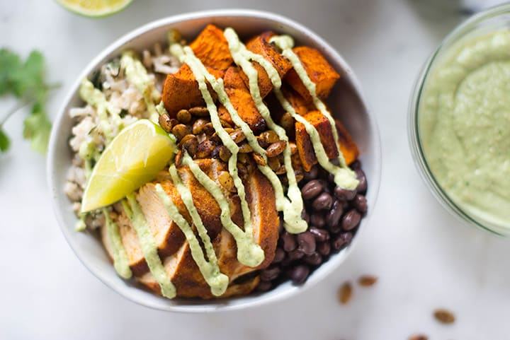 Close up horizontal view of a bowl filled with the cilantro lime rice, roasted sweet potatoes, black beans, toasted pumpkin seeds, and topped with cashew lime crema for the chicken protein bowl.