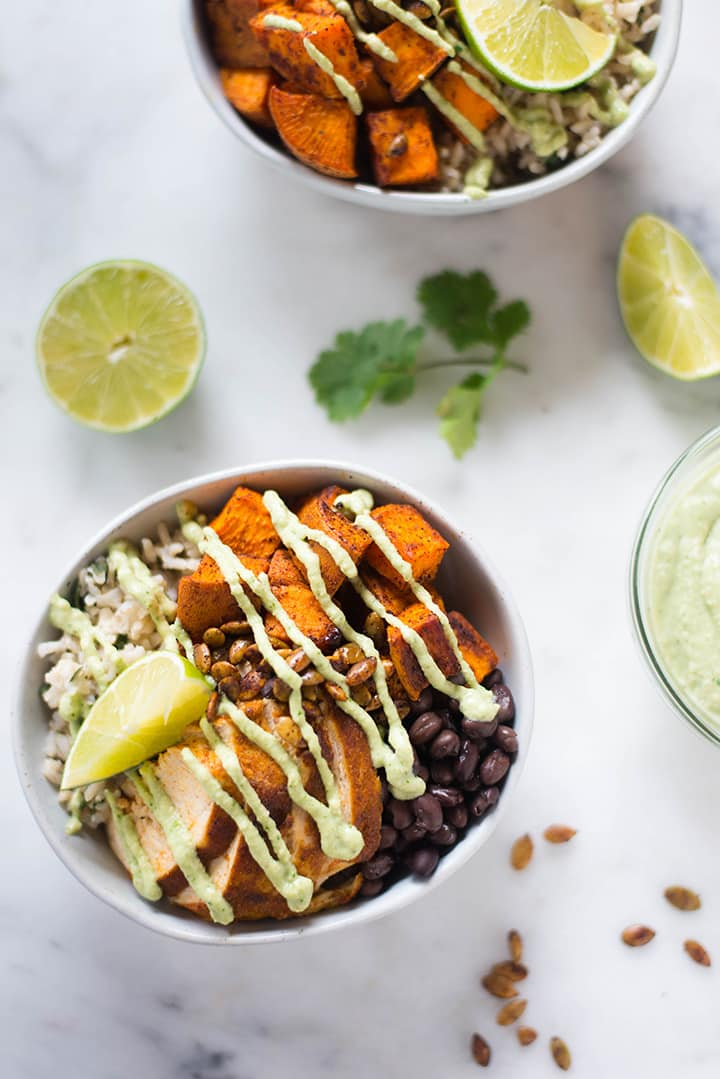 Overhead view of two chicken protein bowls, alongside fresh lime, cilantro, pumpkin seeds, and additional cashew lime crema for topping, a meal to lower blood sugar.