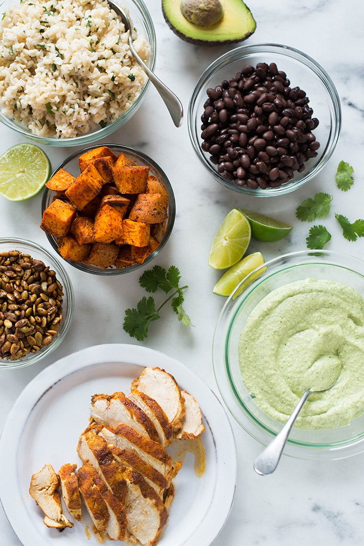 Birds eye view of all the toppings, ready to be used for the chicken protein bowl, including the cilantro lime rice, sliced chicken, cooked black beans, roasted sweet potatoes, cashew lime crema, limes, and toasted pumpkin seeds.