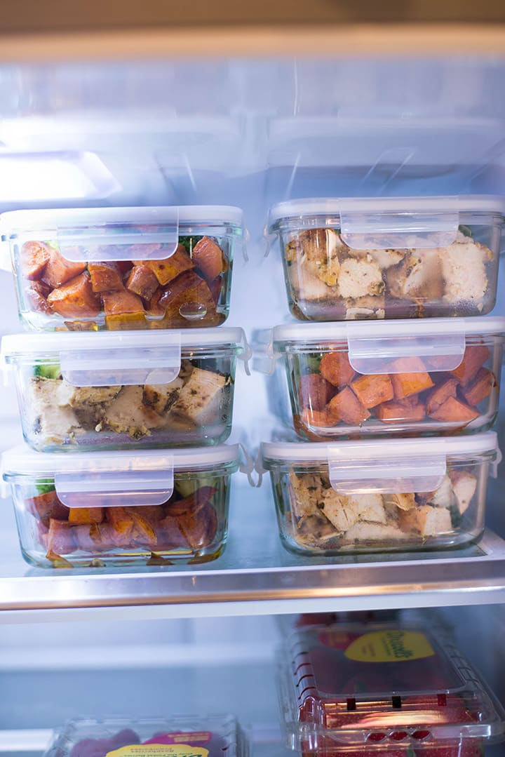 The seven meal prep containers filled with the easy chicken breast recipe that has been meal prepped, roasted sweet potatoes, and sauteed broccoli, to show how to store meal prepped chicken in the fridge.