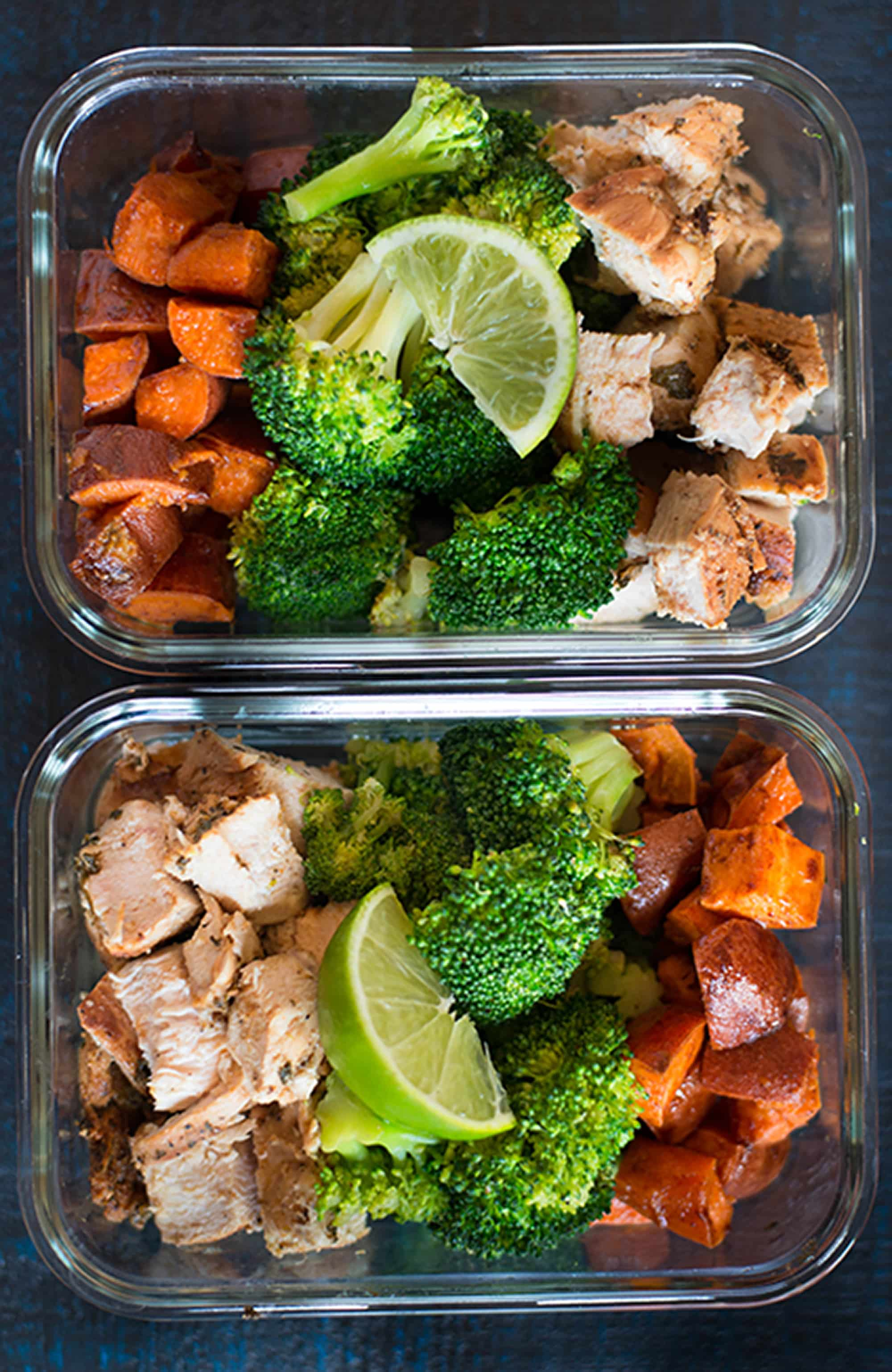 Overhead view of two meal prep containers containing meal prepped chicken, broccoli, and sweet potatoes, to show how to meal prep chicken.