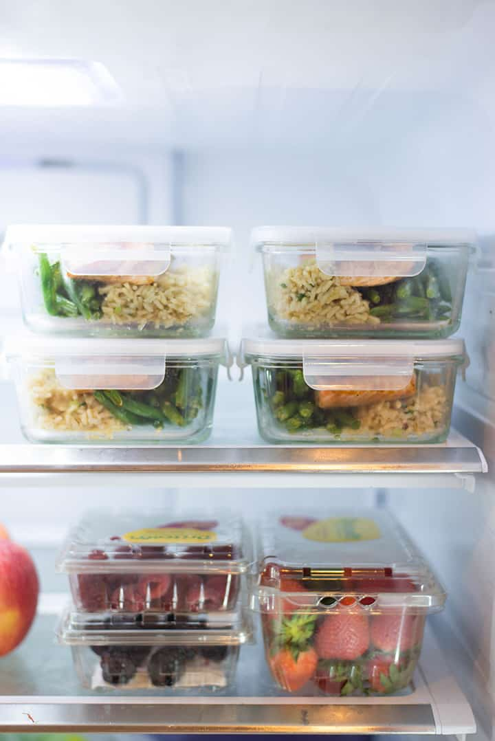 View of the inside of a refrigerator which contains 4 salmon meal prep containers for how to meal prep salmon.