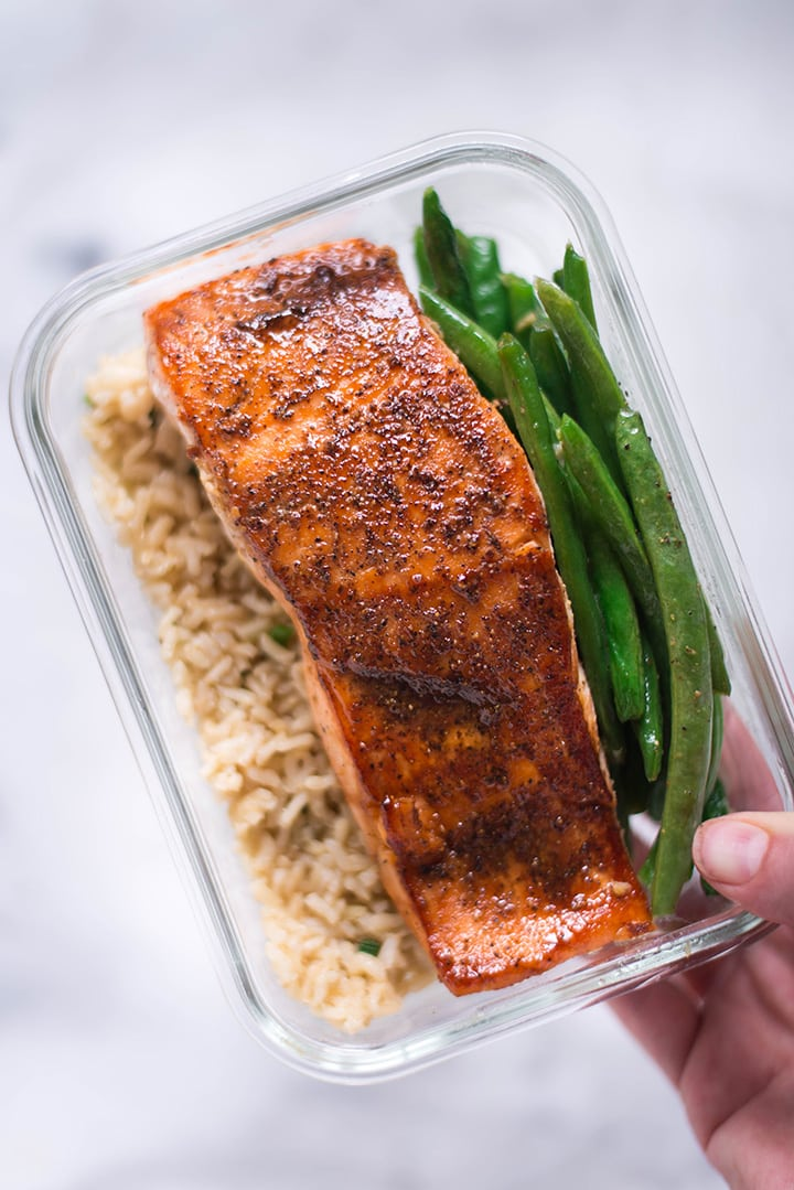 Hand holding a single meal prep container which has pan-roasted salmon, garlic rice, and parmesan garlic green beans for how to meal prep salmon.