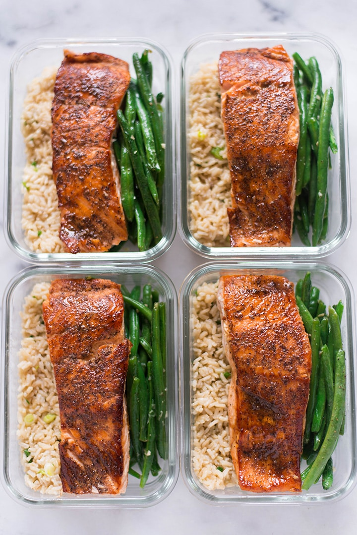 Four meal prep containers, all the same, all filled with garlic rice, garlic parmesan green beans, and pan-roasted salmon for how to meal prep salmon.