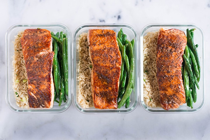 Three meal prep containers in a row, showing the different parts of this easy salmon meal, including green beans, rice, and an easy salmon recipe for how to meal prep salmon.
