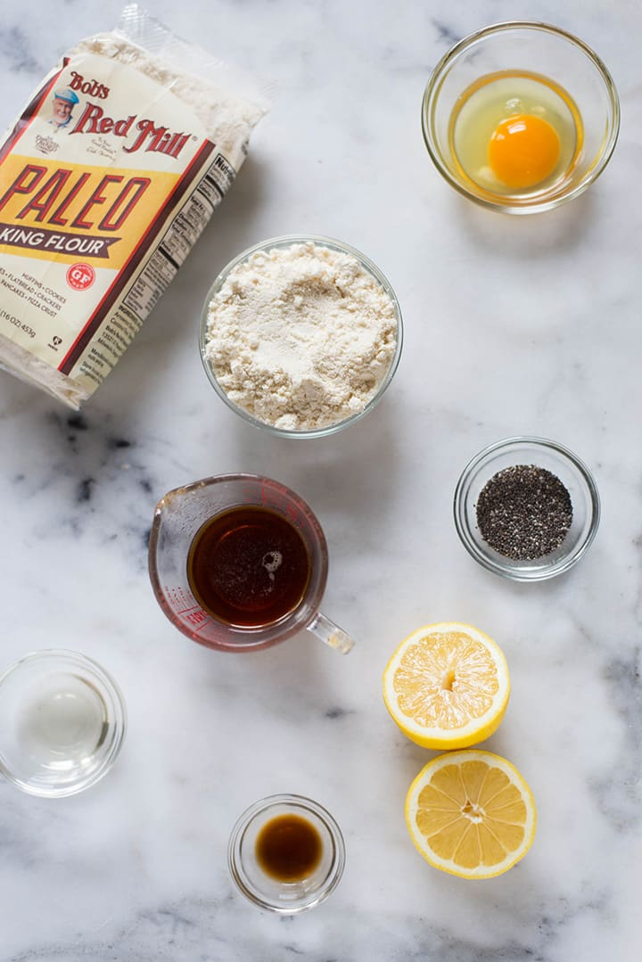 Ingredients needed for chia seed lemon paleo cookies, which includes fresh lemon, lemon zest, chia seeds, paleo baking flour, pure maple syrup, and eggs.