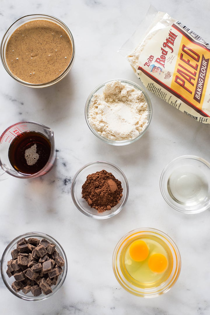 Ingredients needed to make the chocolate chunk paleo cookies, which includes almond butter, chocolate morsels, maple syrup, egg, cocoa powder, coconut oil, and paleo baking flour.