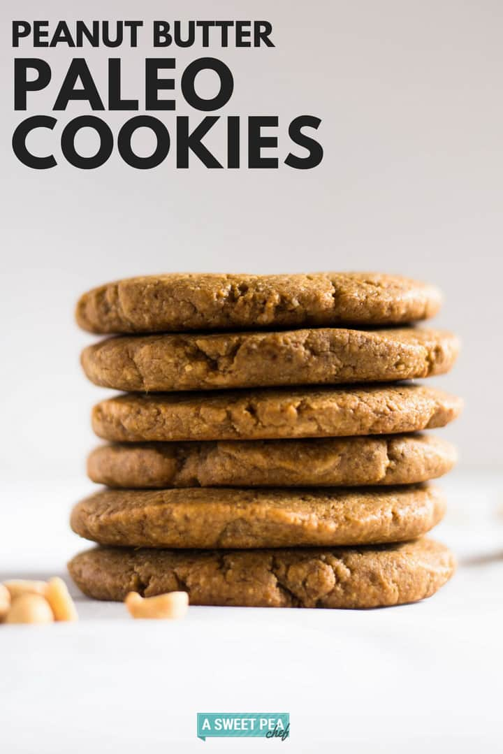 Peanut butter paleo cookies stacked on top of each other, setting next to raw peanuts.