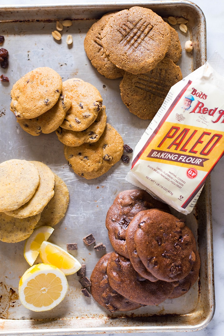 All four paleo cookies laying a rimmed baking sheet next to a bag of paleo baking flour. The four cookies are peanut butter paleo cookies, chia seed lemon cookies, chocolate chunk paleo cookies, and no oatmeal oatmeal raisin cookies.