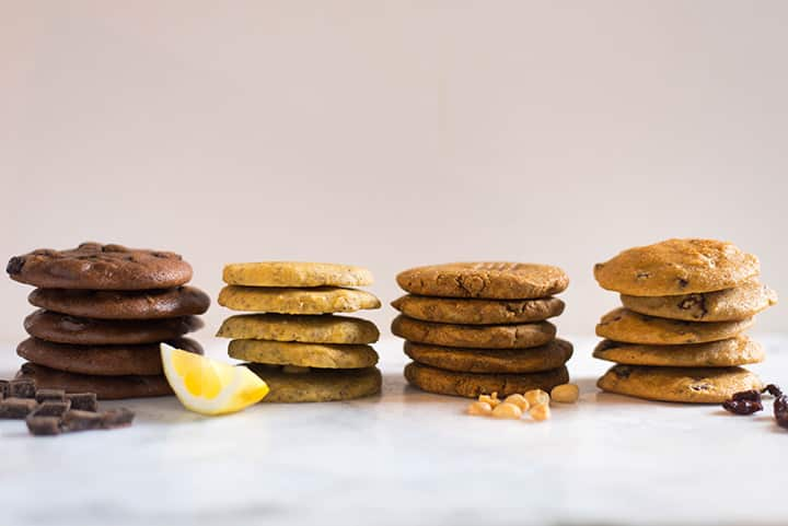 Stacks of paleo cookies in a row, which includes chocolate chunk paleo cookies, chia seed lemon paleo cookies, peanut butter paleo cookies, and no oatmeal oatmeal raisin cookies.