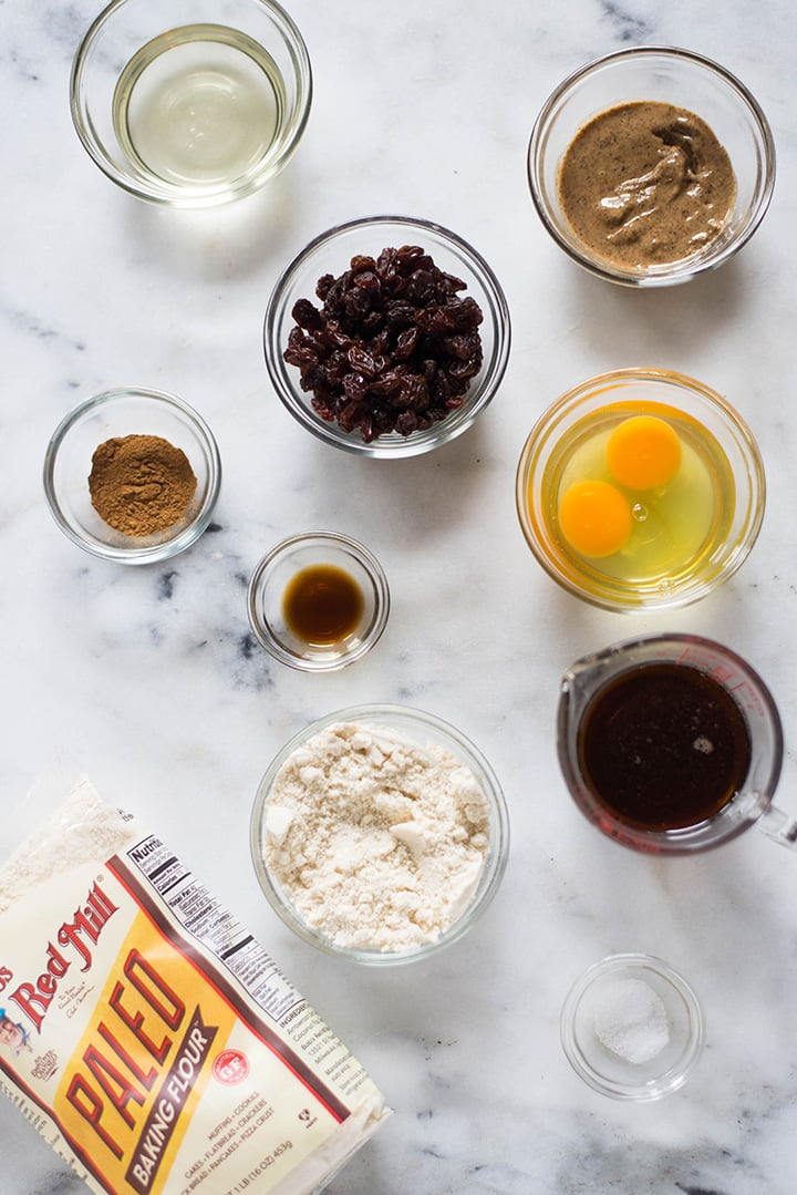 Ingredients needed for the no oatmeal oatmeal raisin paleo cookies, which include eggs, raisins, sea salt, pure maple syrup, paleo baking flour, vanilla extract, and cinnamon.