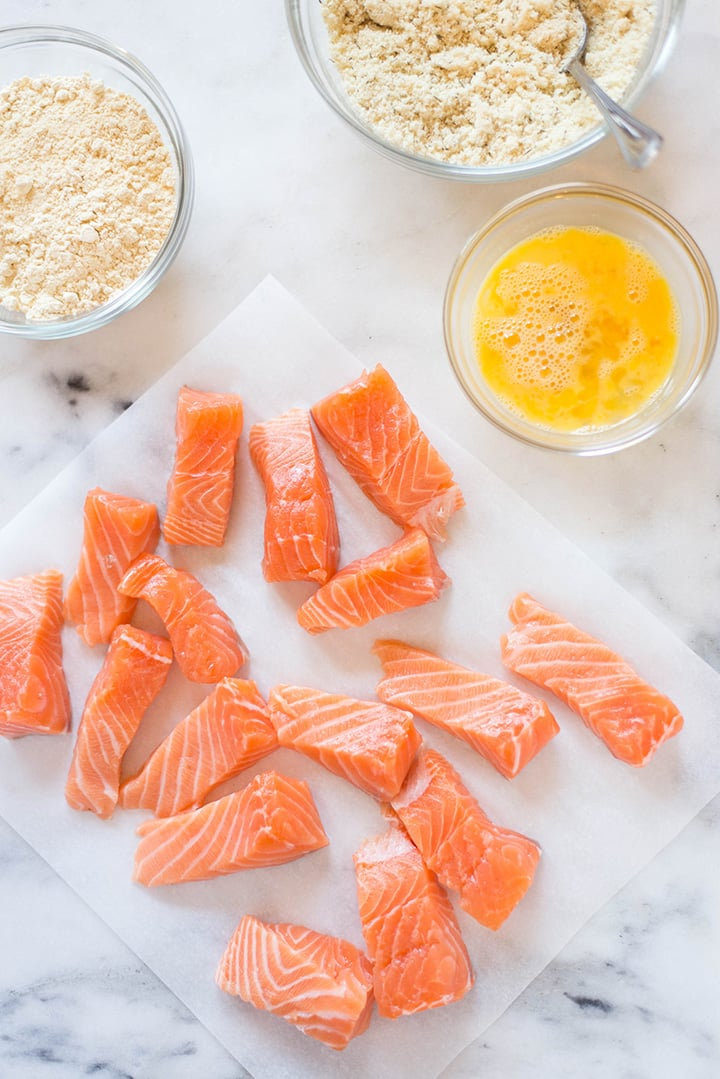 Raw salmon, next to the different coatings to make the homemade fish sticks, including egg and garbanzo flour.