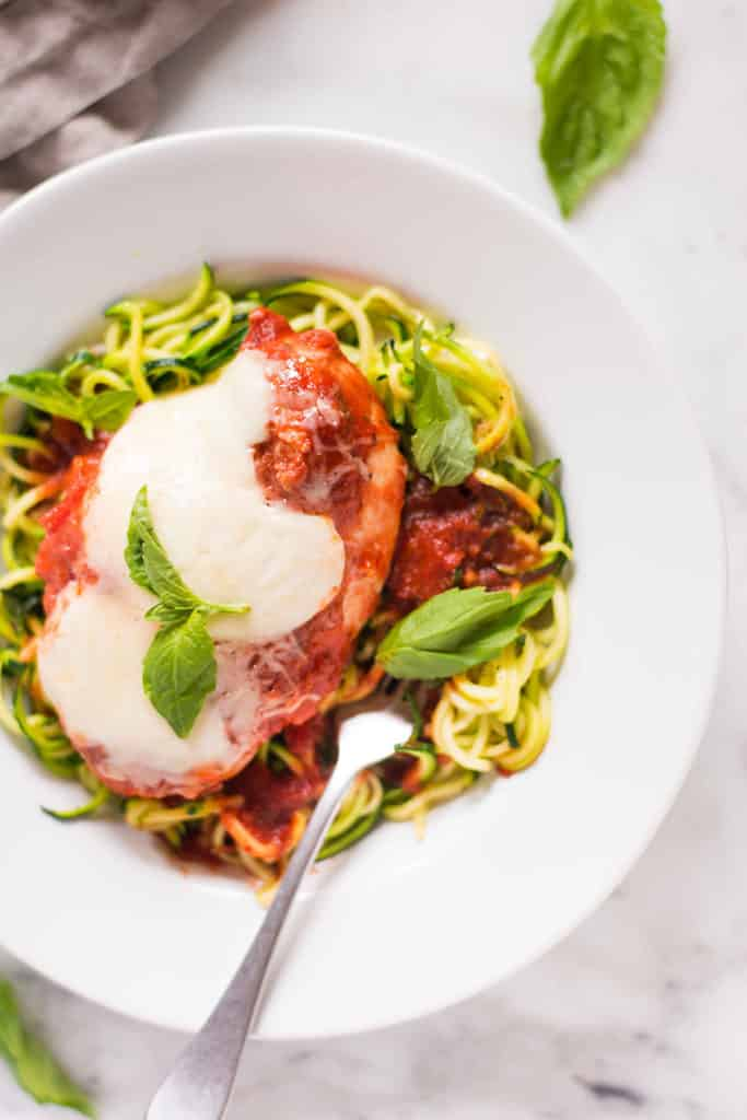 Close up overhead view of Slow Cooker Chicken Parmesan made with zucchini noodles in a white bowl with a fork in place.