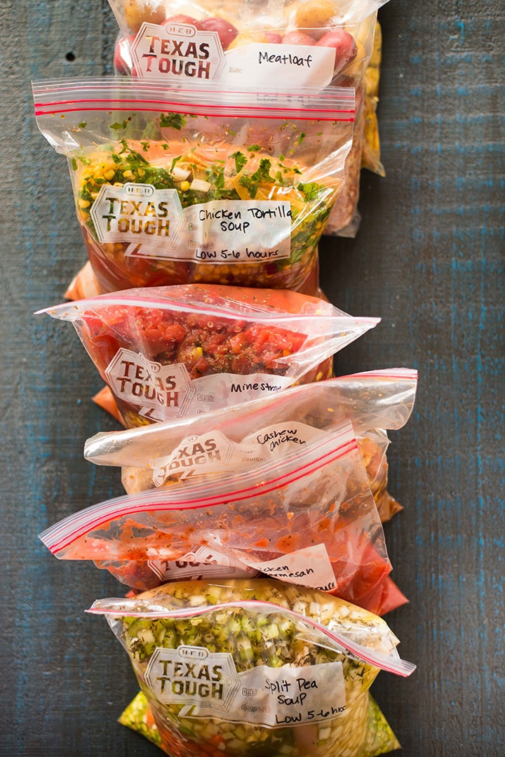 Line of seven slow cooker freezer meals packed into 1 gallon size ziploc freezer nags, ready to freeze.