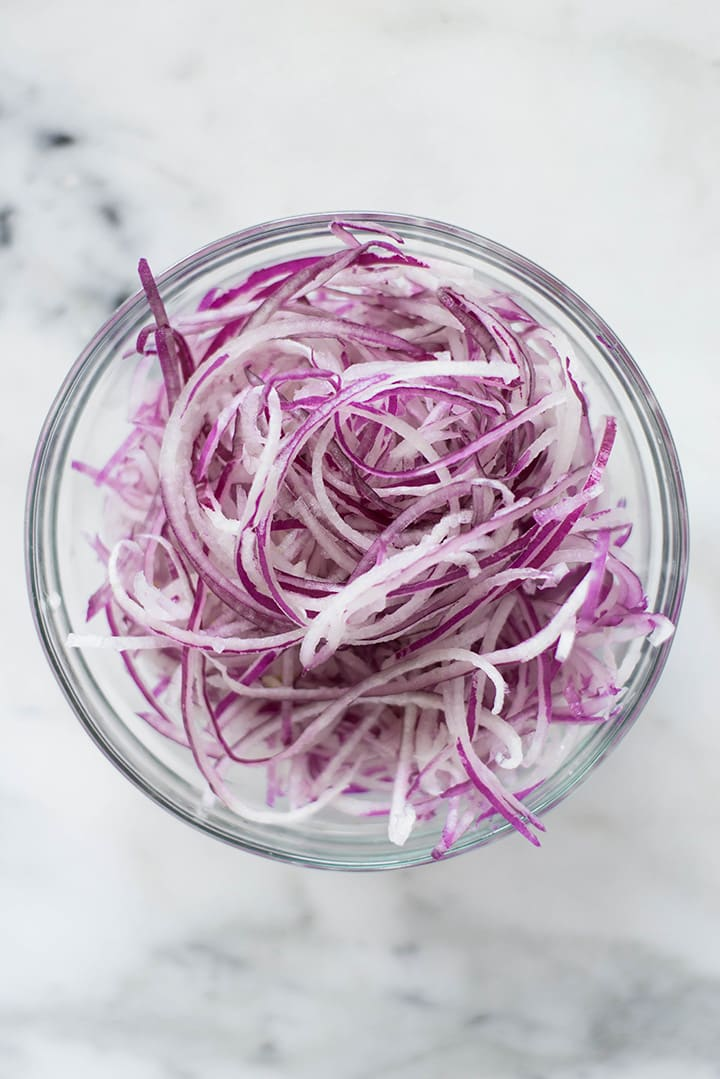 Bowl filled with spiralized red onion noodles to show spiralizer veggie recipe.