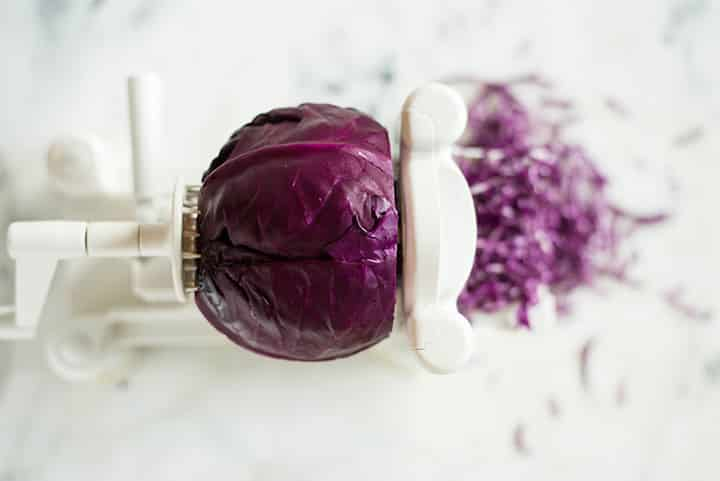 Overhead view of a red cabbage being spiralized to show how to spiralize cabbage.