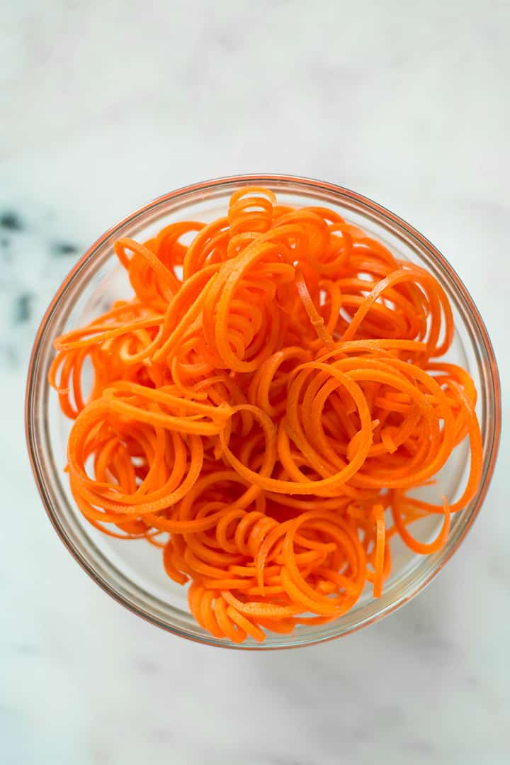 Bowl filled with spiralized carrot noodles to show spiralizer veggie recipe.