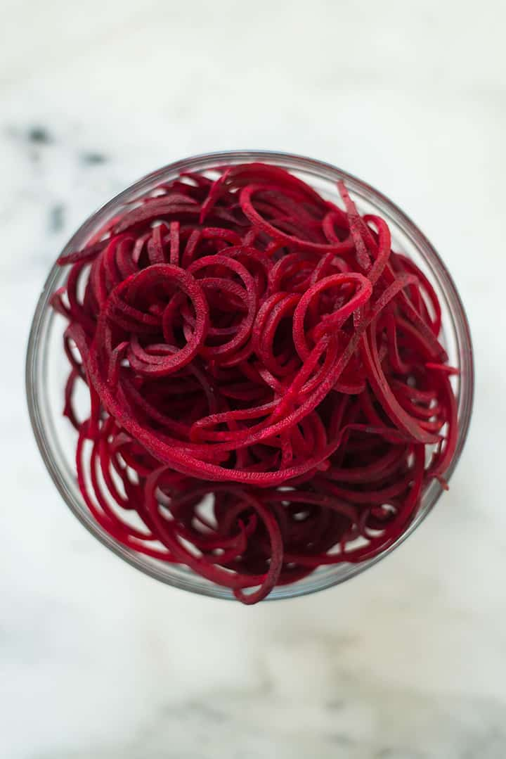 Bowl filled with spiralized beet noodles to show spiralizer veggie recipe.
