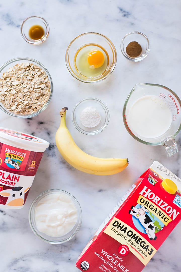 All the ingredients required for how to make banana oat blender pancakes, including rolled oats, banana, baking powder, egg, sea salt, greek yogurt, and milk. Ready to blend.