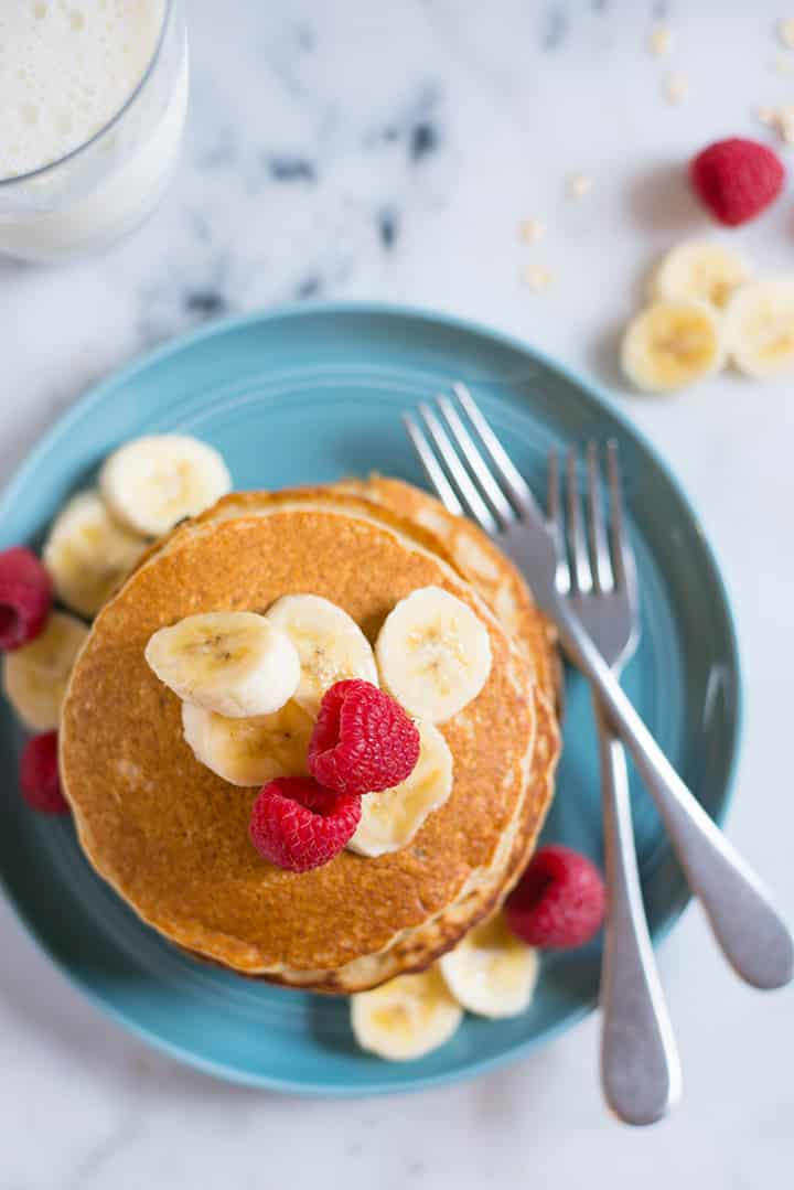 Overhead view of a stack of banana oat blender pancakes that are next to sliced bananas, a glass of milk, and fresh raspberries, ready to eat.