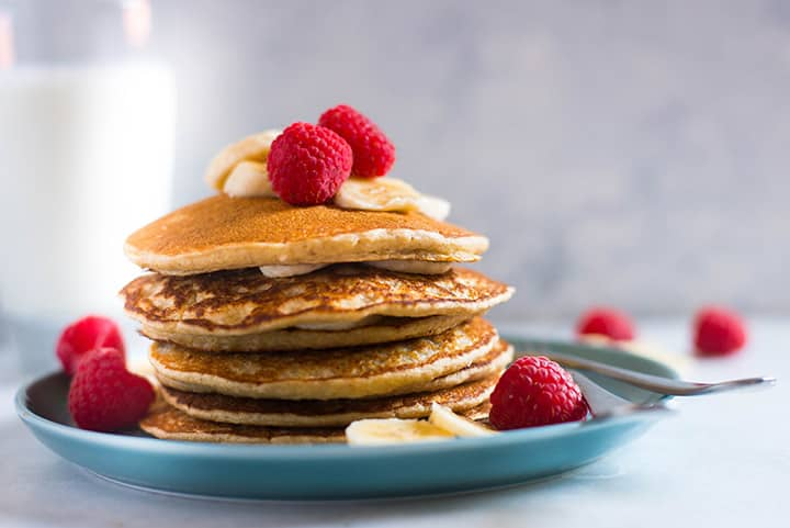 Side view of a large stack of blender oat banana pancakes, topped with fresh raspberries and bananas.