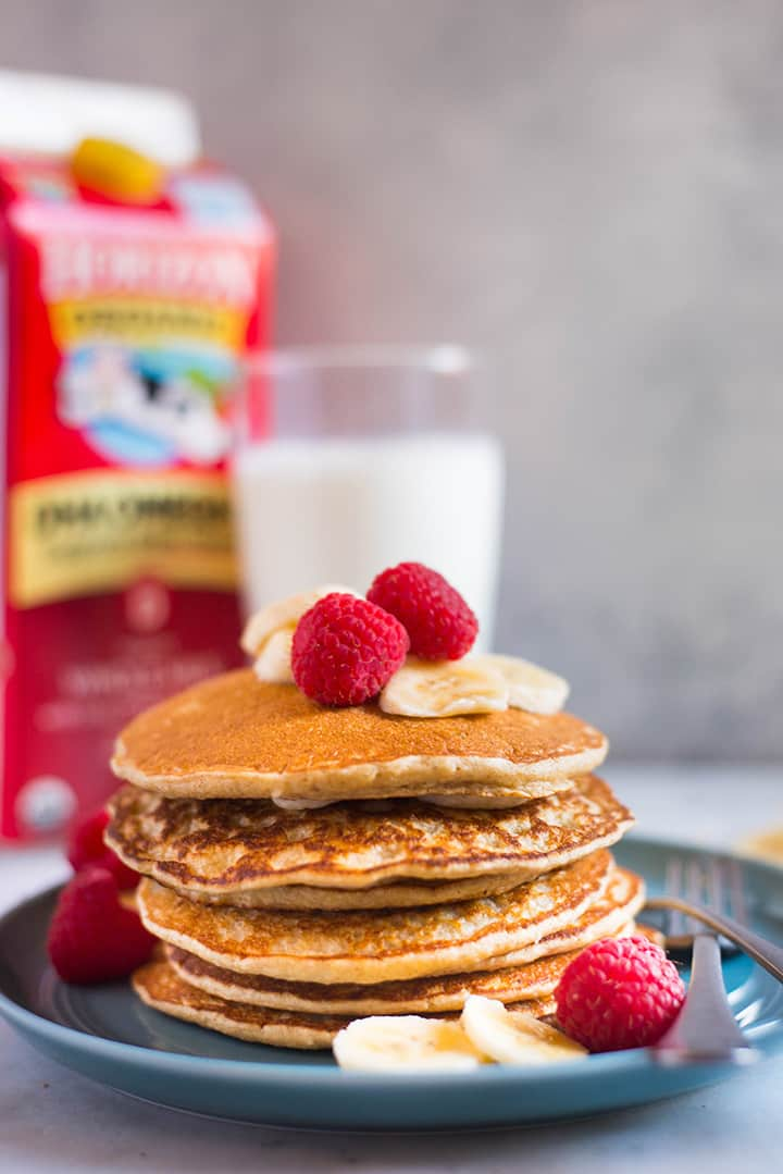Side view of a large stack of banana oat blender pancakes, next to a large glass of milk and a carton of whole milk.