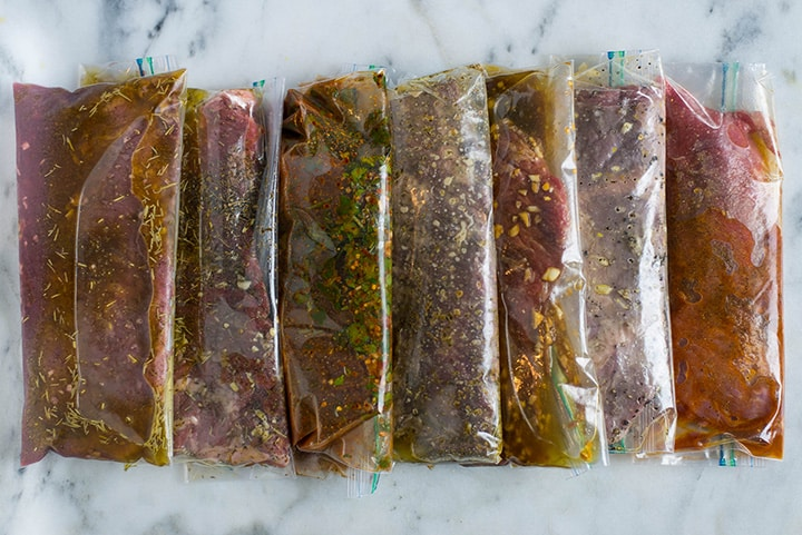 7 sealable freezer bags filled with steak and marinating in different steak marinades, including red wine, Italian, fajita, garlic & herb, ginger soy, lemon pepper, and chipotle.