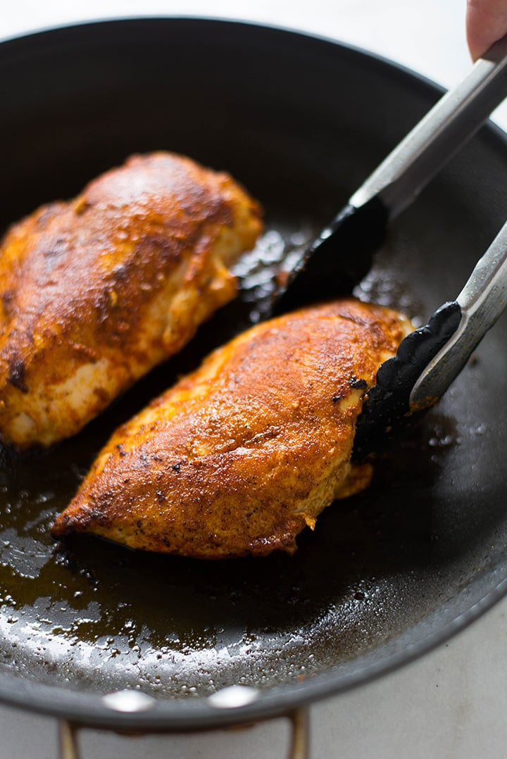 Skillet with two seasoned chicken breasts.