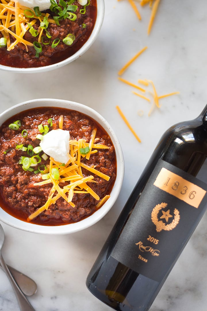 Overhead view of two bowls filled with red Texas chili recipe, topped with green onions, cheddar cheese, and a dollop of greek yogurt, alongside a bottle of red wine which is used in the easy chili recipe.