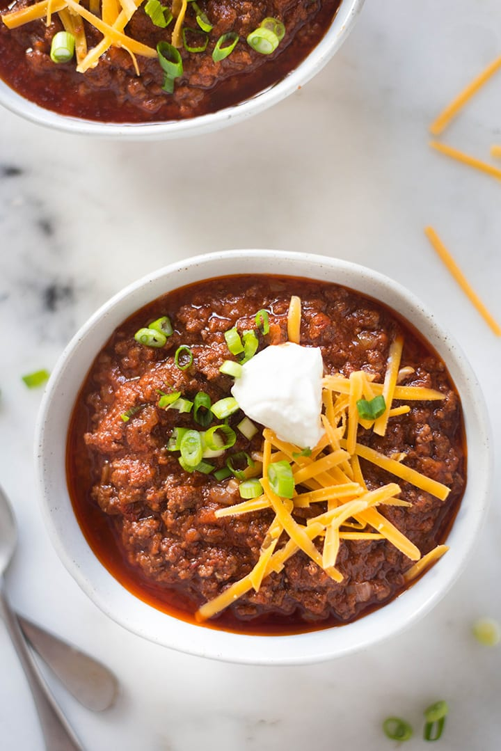 Overhead view of two bowls of the easy Texas Chili, topped with sliced green onions, cheddar cheese, and greek yogurt.