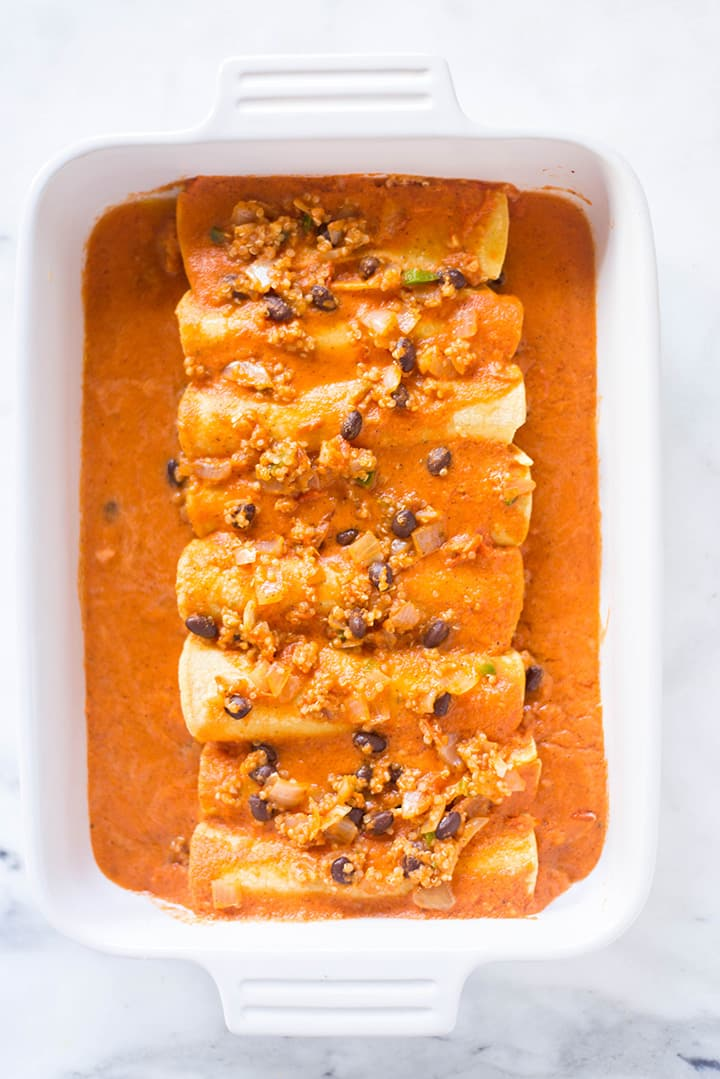 Overhead image of the Spicy Vegan Enchiladas: tortillas with the spicy quinoa and black bean enchilada filling in Homemade Vegan Enchilada Sauce in a casserole dish, ready to be placed in the oven to bake.