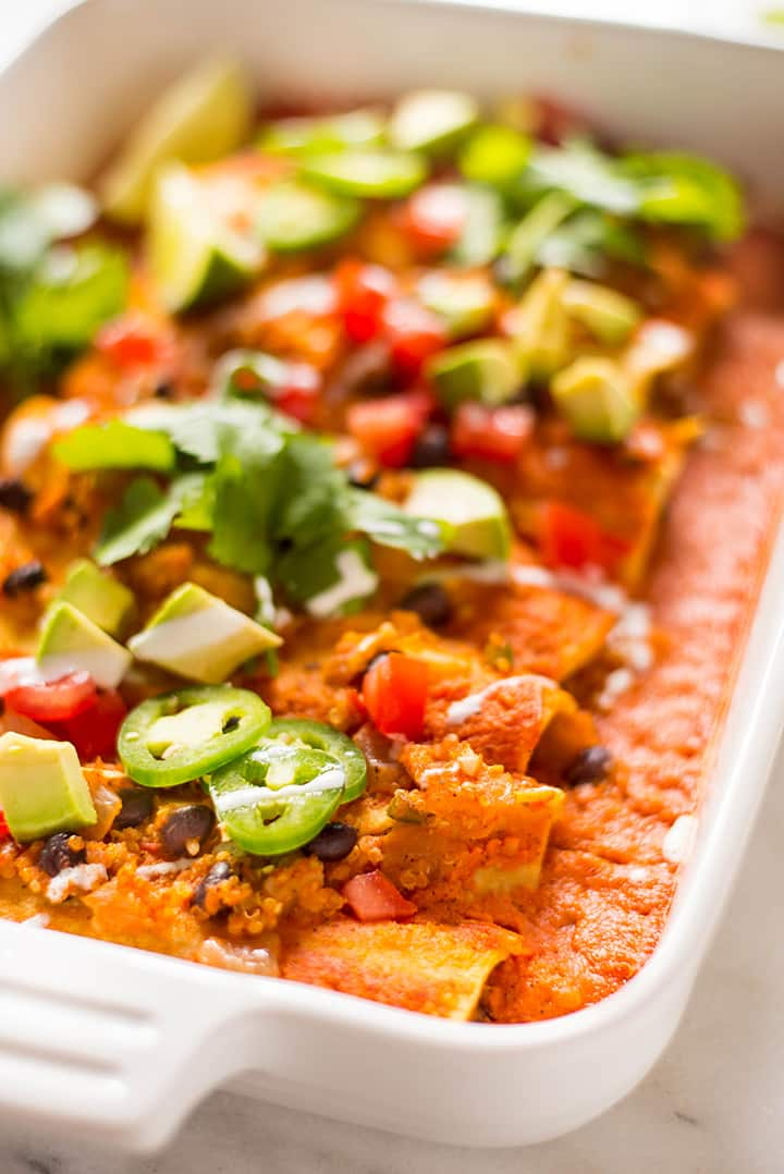 Side angle of a casserole dish filled with the spicy quinoa and black bean vegan enchiladas, topped with tomatoes, jalapenos, cilantro, avocado, and vegan enchilada sauce.