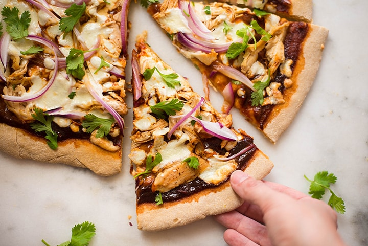 Hand grabbing a slice of the best bbq chicken pizza, which is topped with shredded chicken, fresh mozzarella, homemade clean bbq sauce, sliced red onions, and fresh cilantro.