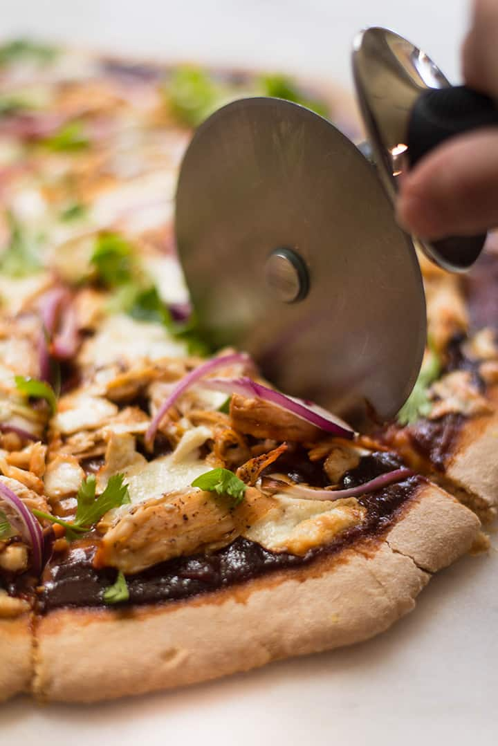 Slicing the best bbq chicken pizza with a pizza cutter.