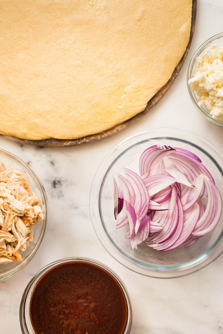 The toppings ready to be added to the whole wheat pizza crust for the best bbq chicken pizza, which include clean barbecue sauce, sliced red onion, fresh mozzarella, and shredded chicken.