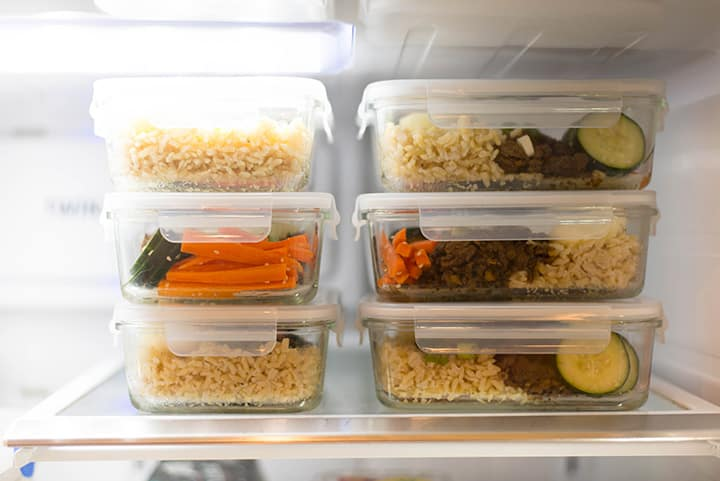 View inside a refrigerator to show the meal prep containers of korean beef bowls, ready to grab and reheat.
