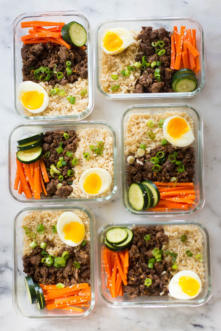 Overhead view of the meal prep korean beef bowls, filled with steamed brown rice, korean ground beef, medium boiled egg, carrot salad, and cucumbers.