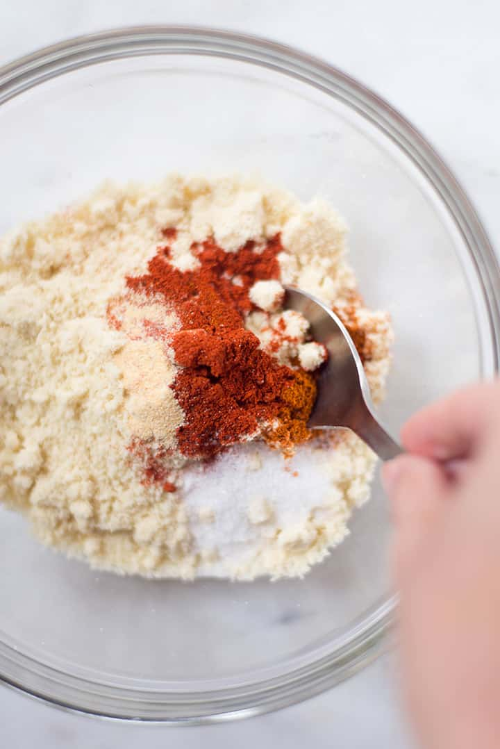Overhead view of a mixing bowl filled with almond meal and spices that is being mixed together to use as a coating for the baked Nashville Hot Chicken.
