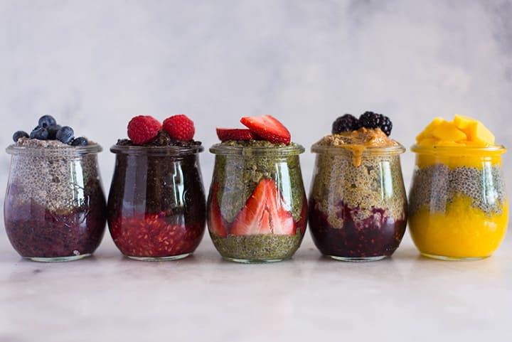 Side view of the 5 best chia pudding recipes, lined up in jars. From left to right is blueberry vanilla chia pudding, raspberry chocolate chia pudding, strawberry matcha chia pudding, pn&j chia pudding, and mango chia pudding.