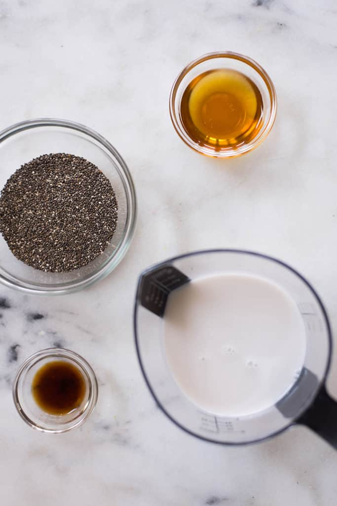 The four basic ingredients for a chia pudding recipe, separated on a counter, including chia seeds, pure maple syrup, vanilla extract, and milk.