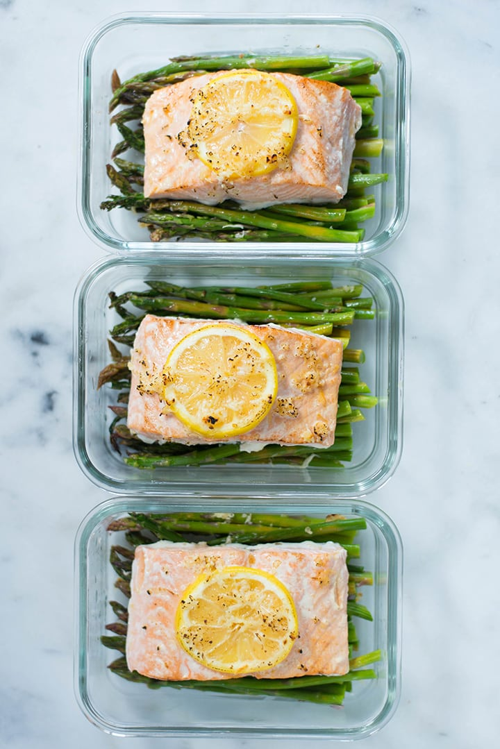 Overhead view of one of the dinners from the meal prep for weight loss, which is asparagus roasted with lemon roasted salmon, organized in meal prep containers.