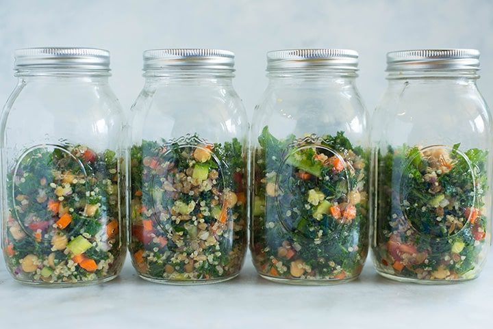 View of one of the lunches from the meal prep for weight loss, which is kale and quinoa salad, stacked in a mason jar.