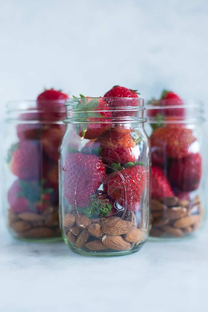 View of one of the snacks for the meal plan for weight loss, which is strawberries and almonds, stacked in a mason jar.