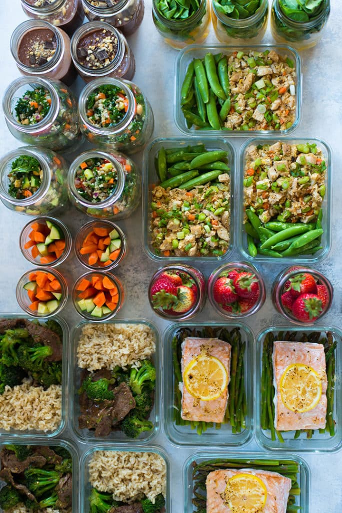Overhead view of the prepped meals for the meal plan for weight loss, all ready to refrigerate in meal prep containers and mason jars.