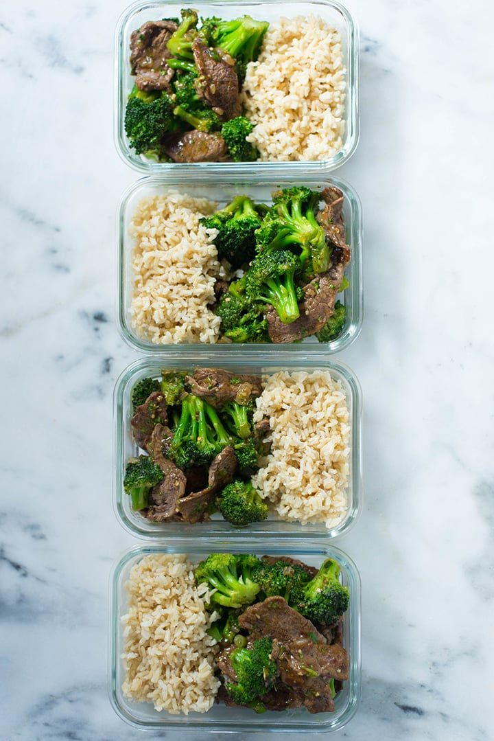 Overview of one of the dinners for the meal prep for weight loss, which is healthy beef and broccoli, organized and divided into four meal prep containers, next to brown rice, ready to refrigerate in meal prep containers.