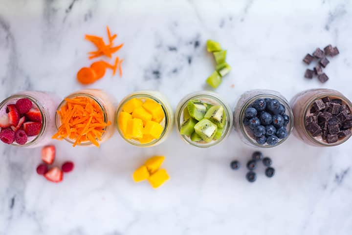 Top view image of jars with Overnight Oats toppings, including sliced berries, shredded carrots, diced mango, sliced kiwi, fresh blueberries, and chocolate.