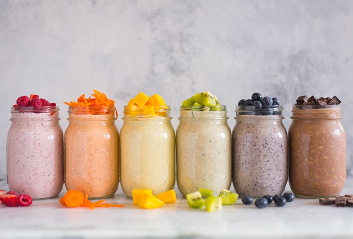 Side view of 6 different mason jars filled with overnight oats recipes, including strawberry overnight oats, carrot cake overnight oats, mango overnight oats, kiwi overnight oats, blueberry overnight oats, and chocolate peanut butter overnight oats.